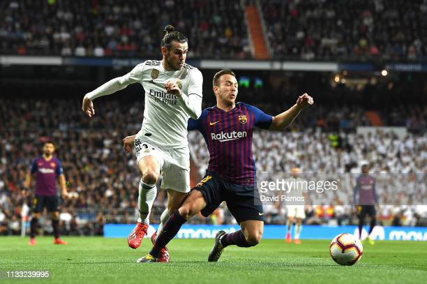Gareth Bale of Real Madrid is tackled by Arthur of Barcelona during the La Liga match between Real Madrid CF and FC Barcelona at Estadio Santiago...