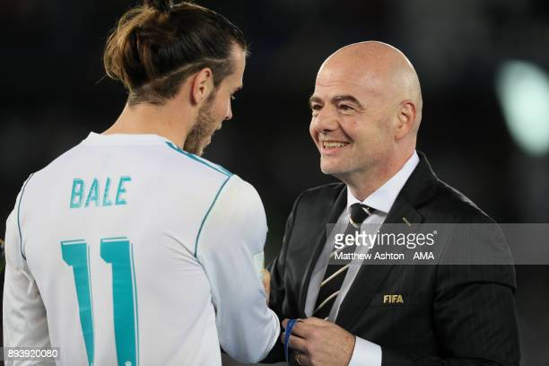 Gareth Bale of Real Madrid receives his winners medal from FIFA President Gianni Infantino at the end of the FIFA Club World Cup UAE 2017 final match...