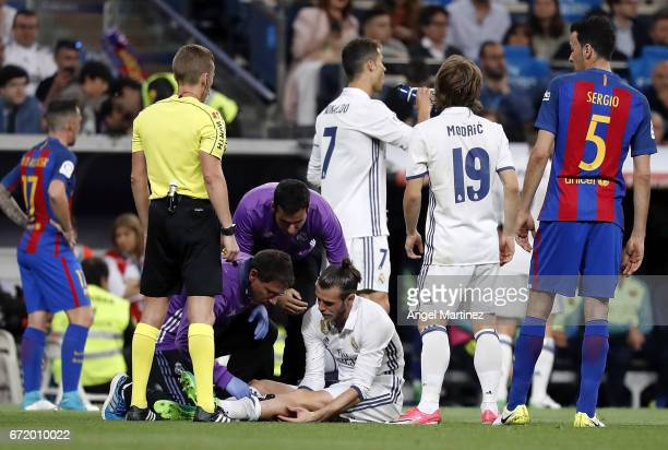 Gareth Bale of Real Madrid receives medical treatment by team doctors during the La Liga match between Real Madrid and FC Barcelona at Estadio...