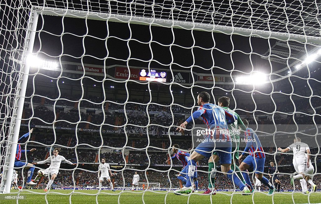 Gareth Bale (L) of Real Madrid scores the opening goal past Diego Marino of Levante UD during the La Liga match between Real Madrid CF and Levante UD at Estadio Santiago Bernabeu on March 15, 2015 in Madrid, Spain.