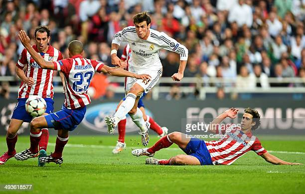 Gareth Bale of Real Madrid shoots wide of the goal under pressure from Miranda and Tiago of Club Atletico de Madrid during the UEFA Champions League...