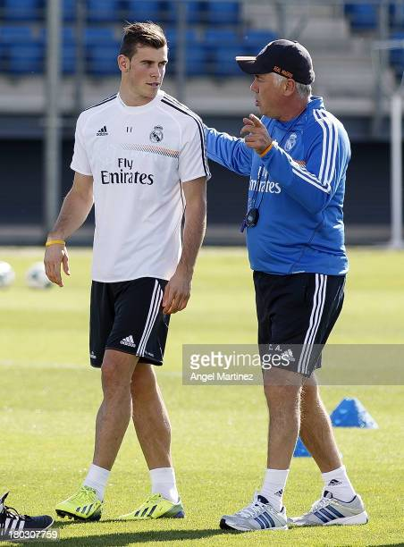Gareth Bale of Real Madrid talks with head coach Carlo Ancelotti during a training session at Valdebebas training ground on September 11, 2013 in...