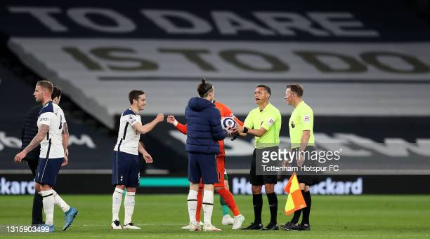 Gareth Bale of Tottenham Hotspur claims the match ball from Referee, Andre Marriner after scoring a hat trick following the Premier League match...