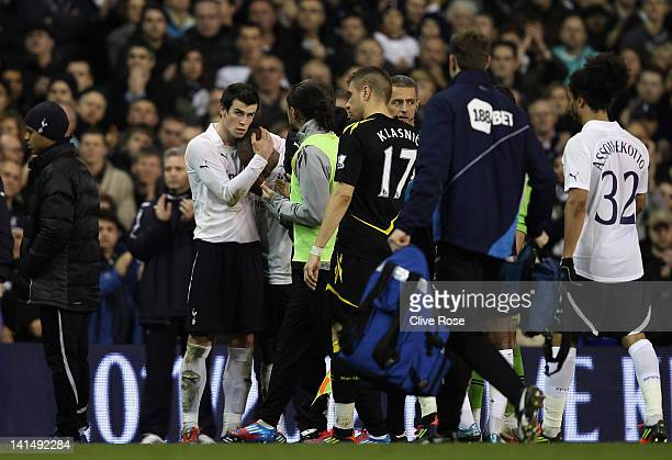 Gareth Bale of Tottenham Hotspur consoles teammate Jermain Defoe after Fabrice Muamba of Bolton Wanderers is taken off on a stretcher still...