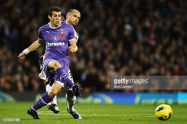 Gareth Bale of Tottenham Hotspur is challenged for the ball by Danny Murphy of Fulham during the Barclays Premier League match between Fulham and...