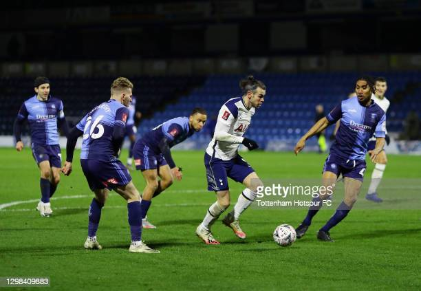 Gareth Bale of Tottenham Hotspur looks to break past Jason McCarthy and Darius Charles of Wycombe Wanderers during The Emirates FA Cup Fourth Round...