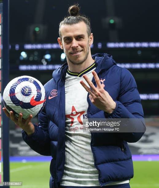 Gareth Bale of Tottenham Hotspur reacts and holds the match ball after scoring a hat trick in the Premier League match between Tottenham Hotspur and...