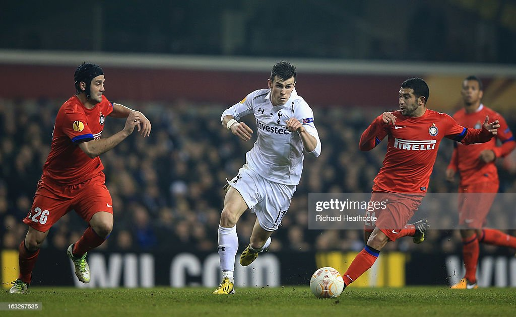 Gareth Bale of Tottenham Hotspur runs with the ball as Cristian Chivu (L) and Walter Gargano of FC Internazionale Milano close him down during the UEFA Europa League Round of 16 First Leg match between Tottenham Hotspur and FC Internazionale Milano at White Hart Lane on March 7, 2013 in London, England.