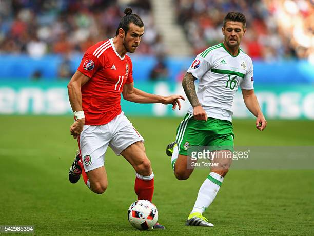 Gareth Bale of Wales and Oliver Norwood of Northern Ireland compete for the ball during the UEFA EURO 2016 round of 16 match between Wales and...