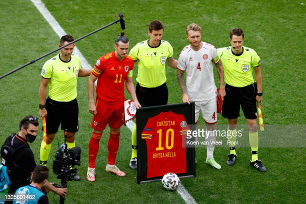 Gareth Bale of Wales and Simon Kjaer of Denmark pose for a photo with a Christian Eriksen of Denmark shirt with Officials, Match Referee, Daniel...