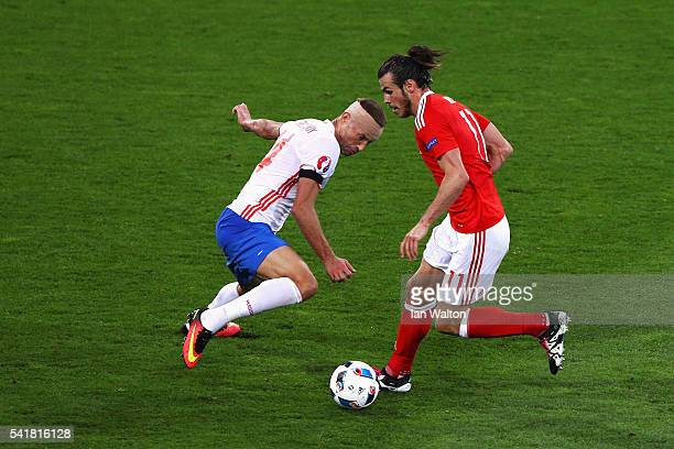 Gareth Bale of Wales and Vasili Berezutski of Russia compete for the ball during the UEFA EURO 2016 Group B match between Russia and Wales at Stadium...