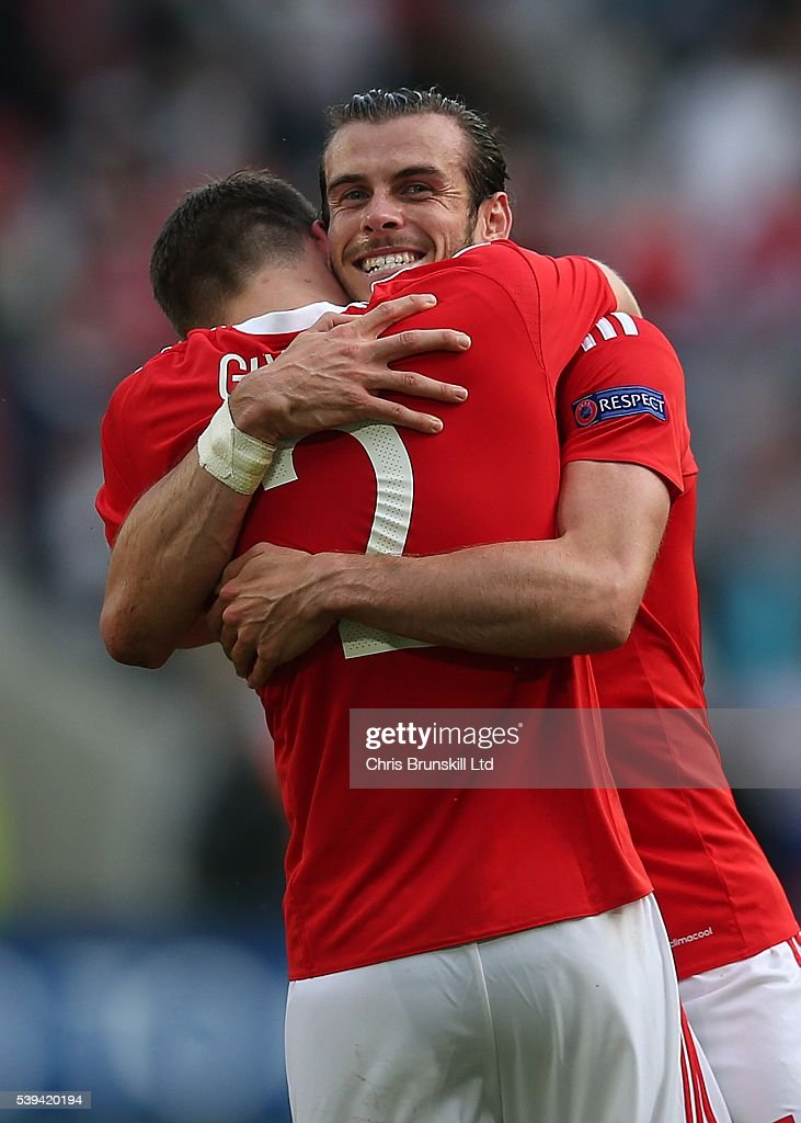 Gareth Bale of Wales celebrates at full-time with team-mate Chris Gunther following the UEFA Euro 2016 Group B match between Wales and Slovakia at Nouveau Stade de Bordeaux on June 11, 2016 in Bordeaux, France.