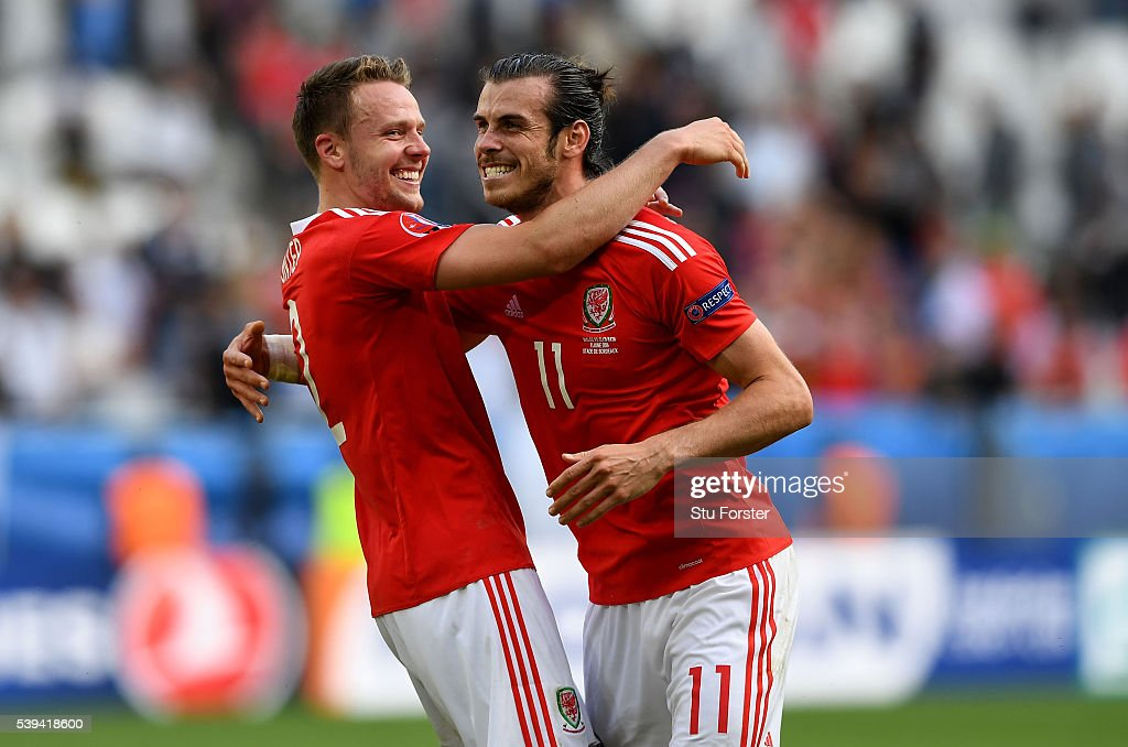 Gareth Bale (R) of Wales celebrates his team's win with his team mate Chris Gunter (L) after the UEFA EURO 2016 Group B match between Wales and Slovakia at Stade Matmut Atlantique on June 11, 2016 in Bordeaux, France.