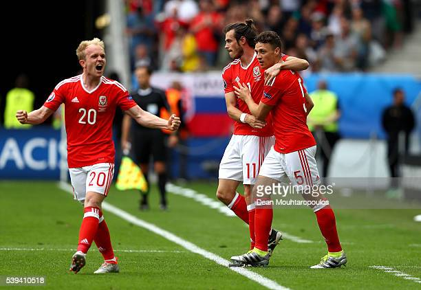 Gareth Bale of Wales celebrates scoring his team's first goal with his team mates Jonathan Williams and James Chester during the UEFA EURO 2016 Group...