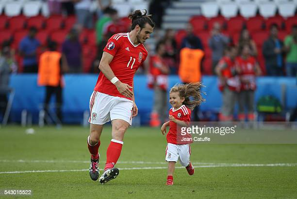 Gareth Bale of Wales celebrates the victory with his daughter Alba Bale on the pitch following the UEFA EURO 2016 round of 16 match between Wales and...