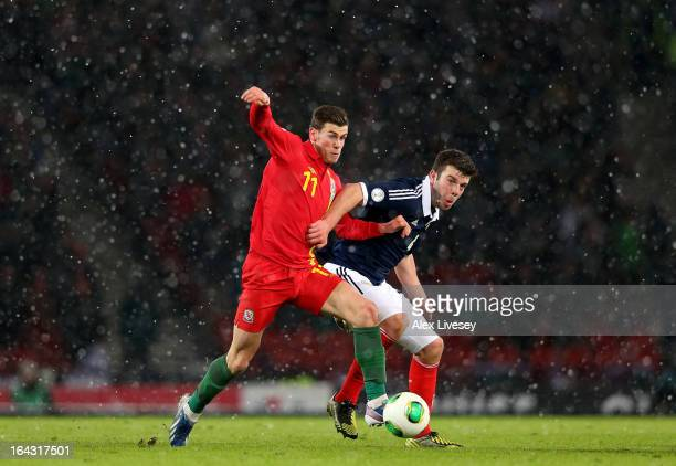 Gareth Bale of Wales holds off a challenge from Grant Hanley of Scotland during the FIFA 2014 World Cup Group A qualifying match between Scotland and...