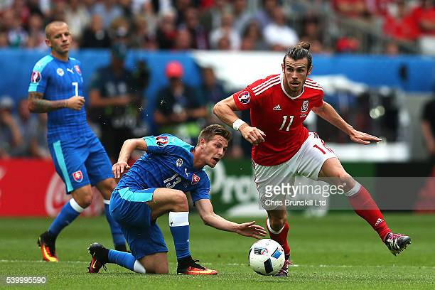 Gareth Bale of Wales in action with Patrik Hrosovsky of Slovakia during the UEFA Euro 2016 Group B match between Wales and Slovakia at Nouveau Stade...