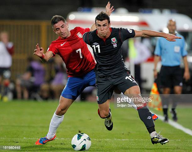 Gareth Bale of Wales is challenged by Zoran Tosic of Serbia during the FIFA 2014 World Cup Qualifier at stadium Karadjordje Park between Serbia and...