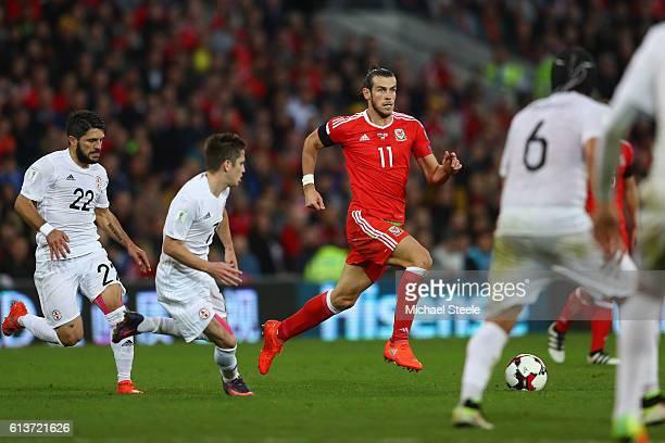 Gareth Bale of Wales is tracked by Giorgi Navalovski Jano Ananidze and Murtaz Daushvili of Georgia during the FIFA 2018 World Cup Qualifier between...