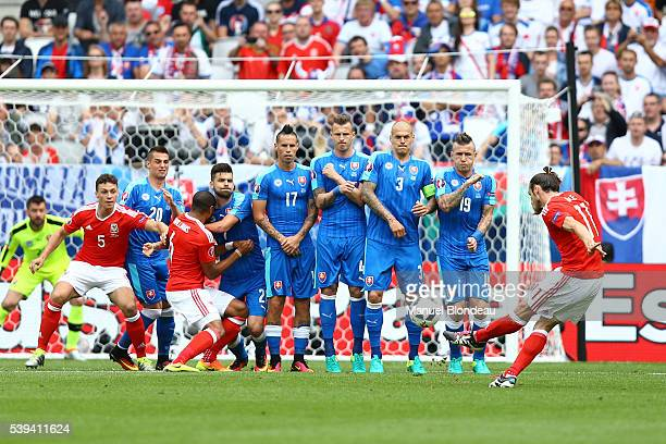 Gareth Bale of Wales kicks the ball to score a goal during GroupB preliminary round between Wales and Slovakia at Stade Matmut Atlantique on June 11...
