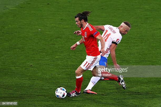 Gareth Bale of Wales runs with the ball past Vasili Berezutski of Russia compete for the ball during the UEFA EURO 2016 Group B match between Russia...