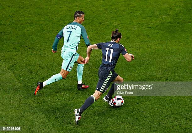 Gareth Bale of Wales runs with the ball under pressure from Cristiano Ronaldo of Portugal during the UEFA EURO 2016 semi final match between Portugal...