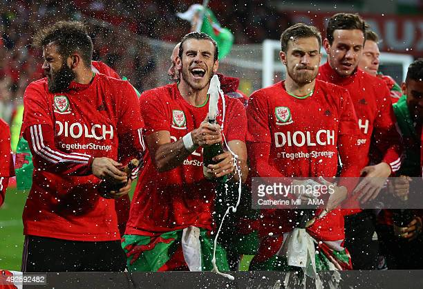 Gareth Bale of Wales sprays champagne as he celebrates alongside Joe Ledley and Aaron Ramsey of Wales after the UEFA EURO 2016 Qualifier match...