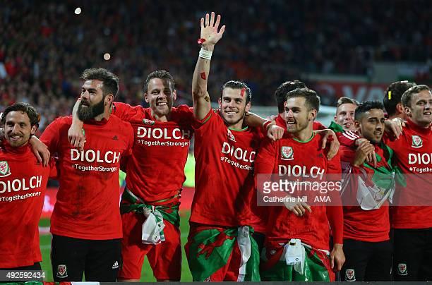 Gareth Bale of Wales waves as he celebrates alongside team mates Joe Ledley Chris Gunter and Aaron Ramsey of Wales after the UEFA EURO 2016 Qualifier...