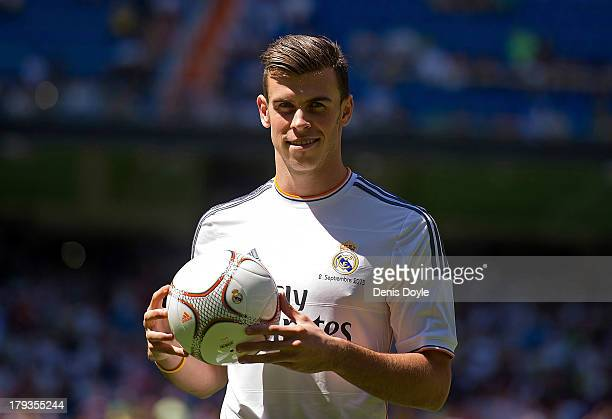 Gareth Bale poses for photographs in his new Real Madrid shirt during his official unveiling at estadio Santiago Bernabeu on September 2 2013 in...