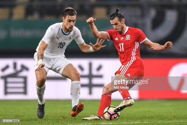 Gareth Bale right of Wales national football team kicks the ball to make a pass against Sebastian Coates of Uruguay national football team in their...
