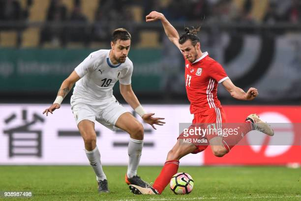 Gareth Bale right of Wales national football team kicks the ball to make a shoot against Sebastian Coates of Uruguay national football team in their...