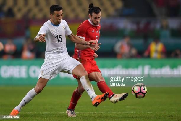 Gareth Bale right of Wales national football team kicks the ball to make a pass against Matias Vecino of Uruguay national football team in their...