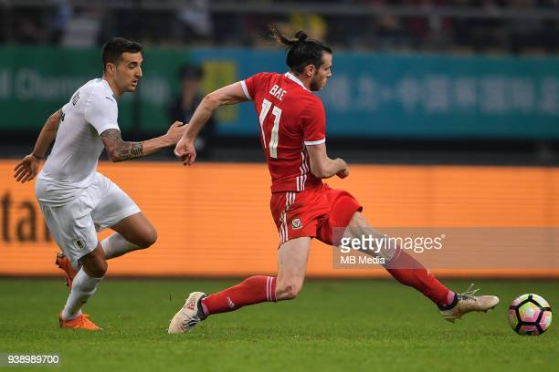 Gareth Bale right of Wales national football team kicks the ball to make a pass against a player of Uruguay national football team in their final...