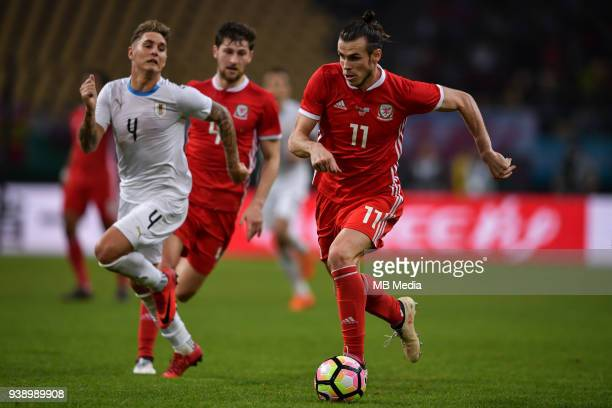 Gareth Bale right of Wales national football team kicks the ball to make a pass against Guillermo Varela of Uruguay national football team in their...