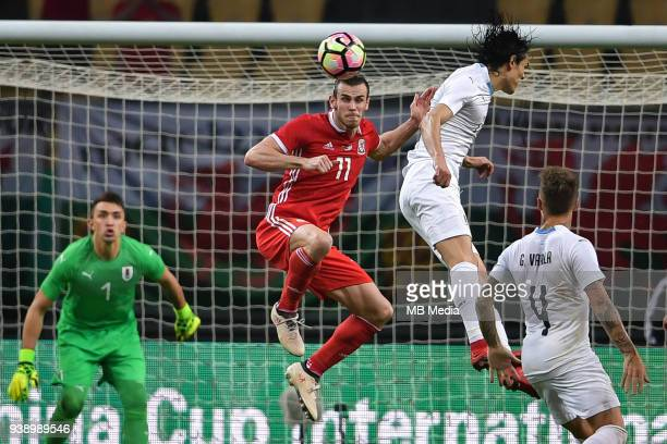 Gareth Bale second top of Wales national football team heads the ball to make a pass against Edinson Cavani of Uruguay national football team in...