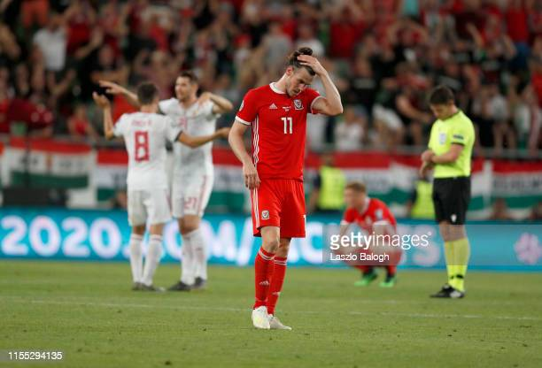 Gareth Bale stands dejected as players from Hungary celebrate at the final whistle following the UEFA Euro 2020 Qualifier between Hungary and Wales...