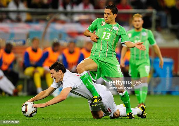 Gareth Barry of England is tackled by Karim Matmour of Algeria during the 2010 FIFA World Cup South Africa Group C match between England and Algeria...