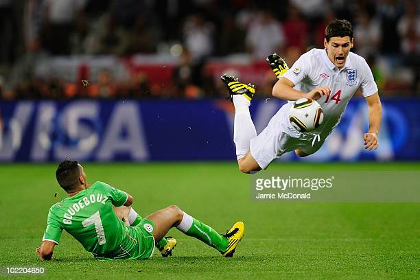 Gareth Barry of England jumps over the tackle by Ryad Boudebouz of Algeria during the 2010 FIFA World Cup South Africa Group C match between England...