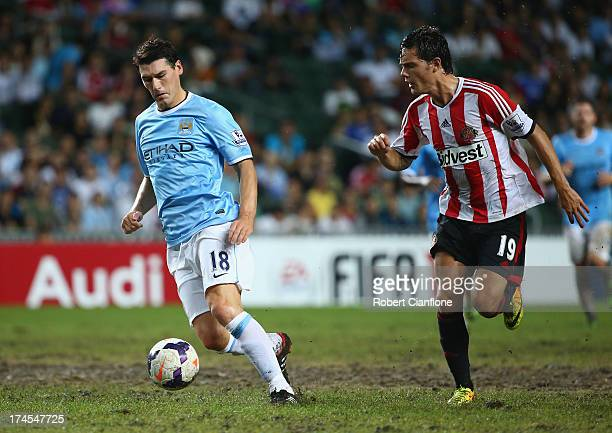 Gareth Barry of Mancester City is chased by David Moberg Karlsson of Sunderland during the Barclays Asia Trophy Final match between Manchester City...