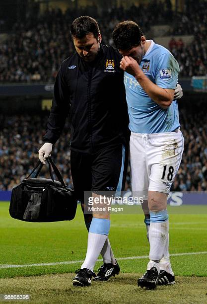 Gareth Barry of Manchester City is helped from the pitch with an injury during the Barclays Premier League match between Manchester City and...