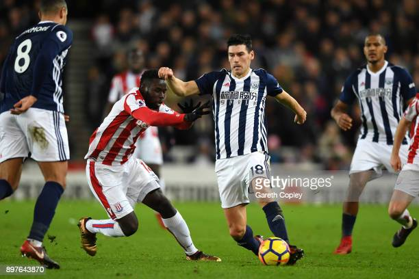 Gareth Barry of West Bromwich Albion is challenged by Mame Biram Diouf of Stoke City during the Premier League match between Stoke City and West...