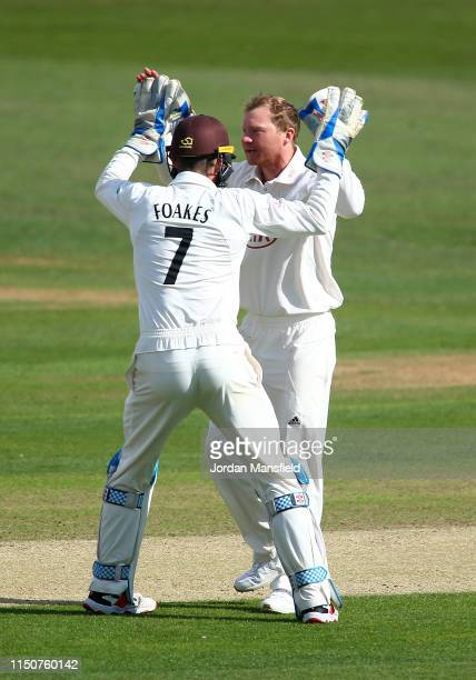 Gareth Batty of Surrey celebrates with Ben Foakes of Surrey after dismissing Ollie Robinson of Kent during day two of the Specsavers County...