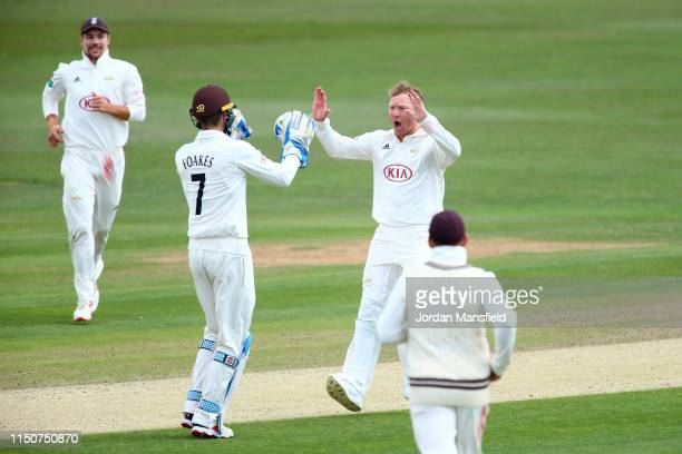 Gareth Batty of Surrey celebrates with his teammates after dismissing Daniel Bell-Drummond of Kent during day two of the Specsavers County...