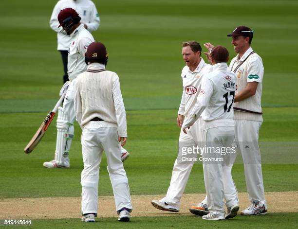 Gareth Batty of Surrey celebrates with team mates after taking the wicket of Marcus Trescothick of Somerset during day one of the Specsavers County...