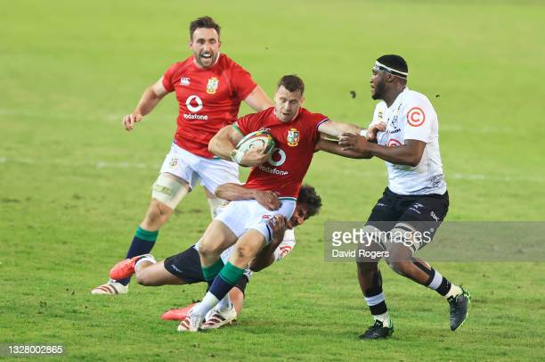 Gareth Davies of The British and Irish Lions is tackled by Lionel Cronje and Mpilo Gumede of Cell C Sharks during the tour match between Cell C...