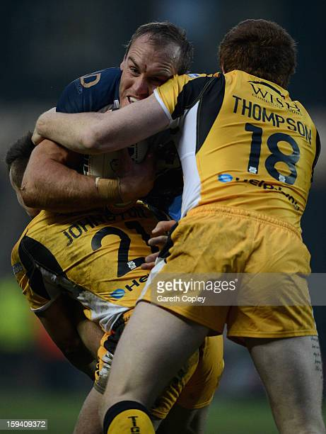 Gareth Ellis of Hull FC is tackled by Ben Johnson and Jordan Thompson of Castleford during a preseason friendly match between Hull FC and Castleford...
