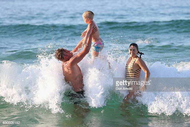 Gareth, Indy and Lauren Morton, from Aberfeldy, Scotland, frolic in the surf at Bondi Beach on December 25, 2016 in Sydney, Australia. Bondi Beach is...