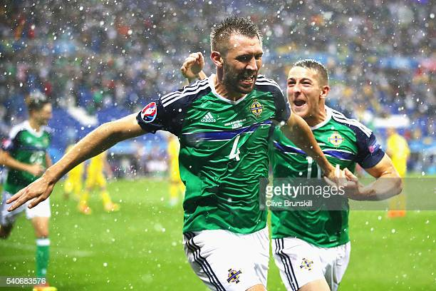 Gareth McAuley of Northern Ireland celebrates scoring his team's first goal with his team mate Conor Washington during the UEFA EURO 2016 Group C...