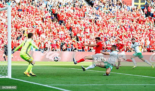 Gareth McAuley of Northern Ireland scores an own goal past Michael McGovern during the UEFA EURO 2016 round of 16 match between Wales and Northern...