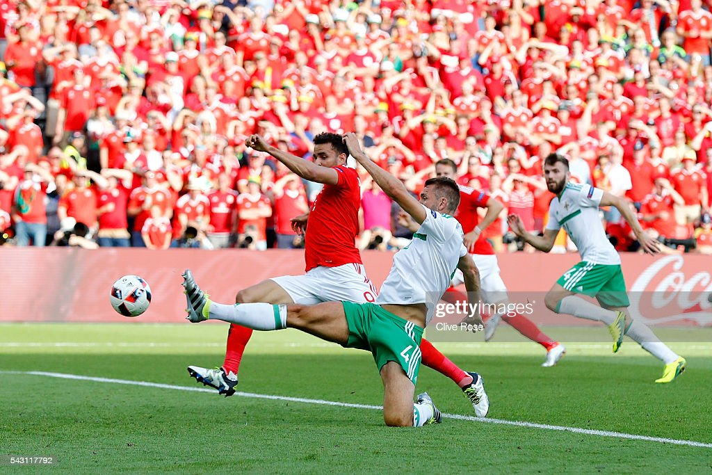 Gareth McAuley (3rd R) of Northern Ireland scores an own goal past Michael McGovern (1st L) during the UEFA EURO 2016 round of 16 match between Wales and Northern Ireland at Parc des Princes on June 25, 2016 in Paris, France.